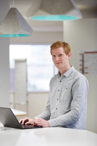 Young man with red hair wearing a light blue shirt using a laptonJames McClean_IRE_2016_MB_01.jpg
